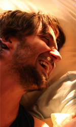 La fotogallery del film Un altro mondo - Andrea e Charlie ridono sdraiati insieme sul letto.