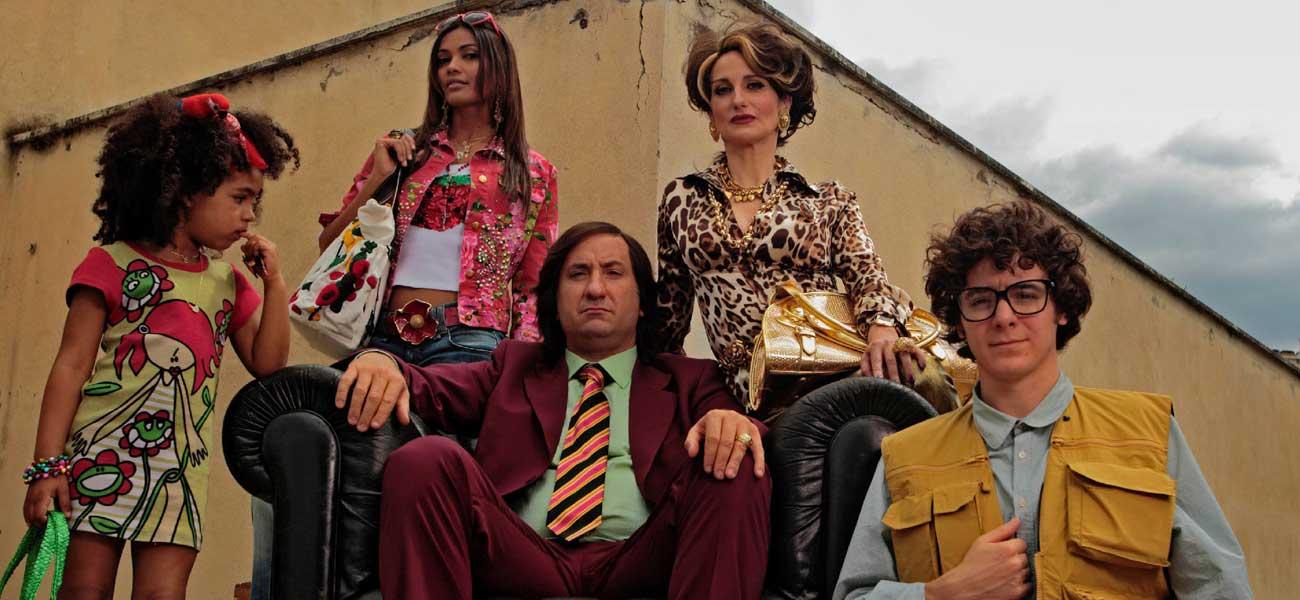 Abbigliamento ricercato, originale e sopra le righe per Cetto La Qualunque e consorte che per farsi notare dagli elettori indossano colori accesi e accessori brillanti.