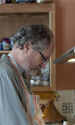 La fotogallery del film Another Year - Gerri abbraccia il marito impegnato ai fornelli.