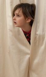 The Wholly Family, le foto - Il piccolo Jack dietro le tende in una scena del film <em>The Wholly Family</em>.