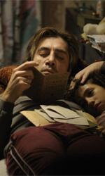 La fotogallery del film Biutiful - Uxbal legge sdraiato sul divano insieme ad Ana. Mateo è seduto a tavola.