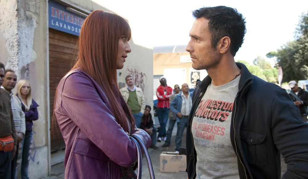 Eva e Giulio in una scena del film.  I due sono in piedi, in strada, e stanno parlando. Hanno due facce serie.