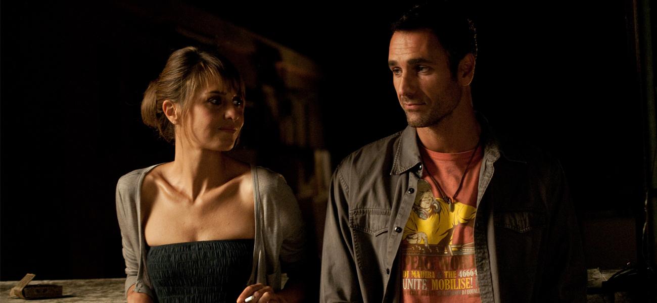Paola Cortellesi e Raoul Bova in una scena di Nessuno mi può Giudicare. I due sono in piedi uno accanto all'altro, appoggiati ad un muretto. E' notte. Lui guarda nel vuoto e lei guarda il volto dell'uomo.